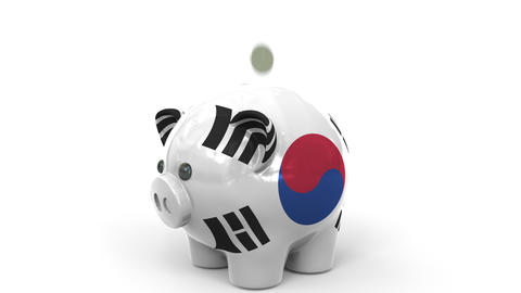 Coins fall into piggy bank painted with flag of South Korea. National banking Live Action