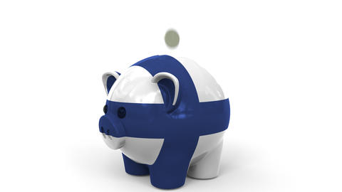 Coins fall into piggy bank painted with flag of Finland. National banking system Live Action