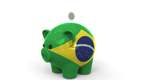 Coins fall into piggy bank painted with flag of Brazil. National banking system Live Action