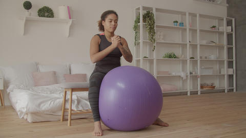 Determined female exercising with fitball at home Live Action