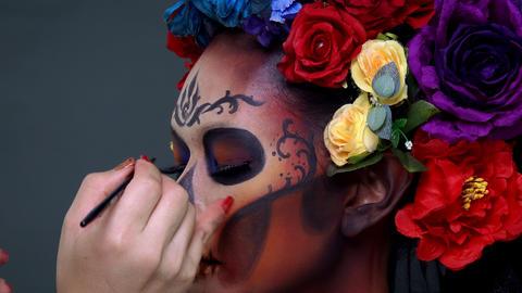 Closeup makeup artist draw a sugar skull pattern on female model's face Footage