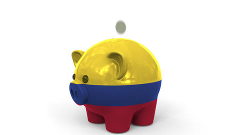 Coins fall into piggy bank painted with flag of Colombia. National banking Live Action
