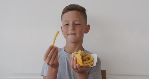 Happy little child boy eating french fries. Health care and food concept Live Action