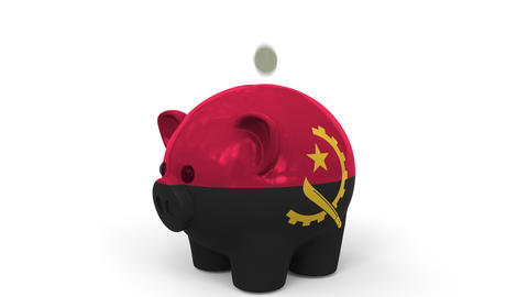 Coins fall into piggy bank painted with flag of Angola. National banking system Live Action