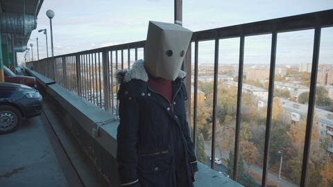 Girl with a package on the head at the multi-storey car park. Girl in a jacket Live Action