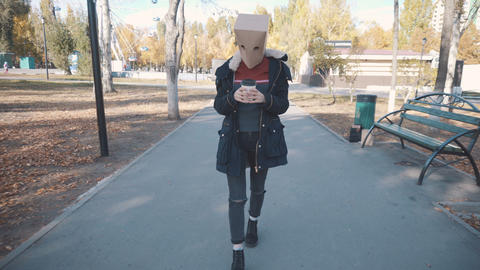 Girl with a package on her head walks with a cup of coffee. Girl in a jacket Live Action