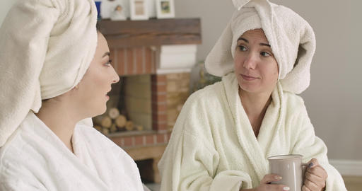 Portrait of two positive Caucasian women in bathrobes and hair towels sitting at Footage