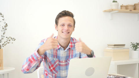 Happy designer giving thumbs up to camera in creative office Footage