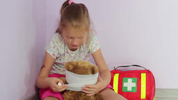 First Aid. Girl is wrapping teddy bear head with bandage. Close up shot Footage