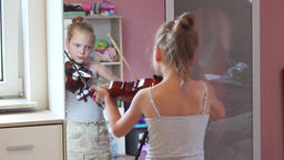 Young schoolgirl is practising playing viola at home. Rack focus Footage