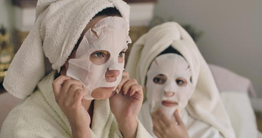 Two adult Caucasian women taking off face masks. Beautiful girls in hair towels Footage