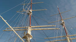 Rolled up sails at the sailing ship. Blue sky background Live Action