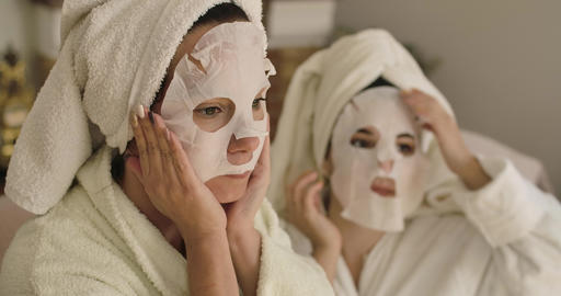 Portrait of two adult Caucasian women applying face masks. Positive girls in Footage