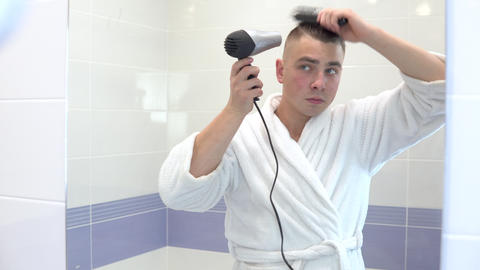 A young man dries his hair with a hairdryer. A man in a white coat makes styling Live Action