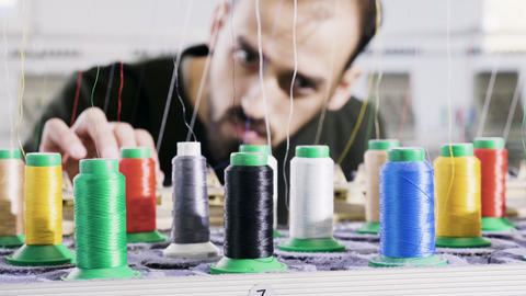 Man in a fabric factory checking the sewing thread Live Action