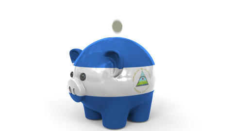 Coins fall into piggy bank painted with flag of Nicaragua. National banking Live Action