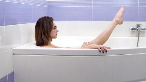 A young woman with glasses lies in the bath. The girl relaxes in the bath and Footage