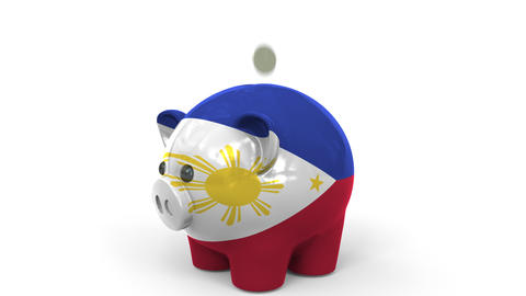 Coins fall into piggy bank painted with flag of Philippines. National banking Live Action