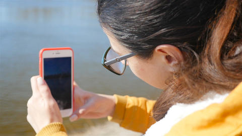 Beautiful girl photographs the river with a smartphone. Close-up. Sunny weather Live Action
