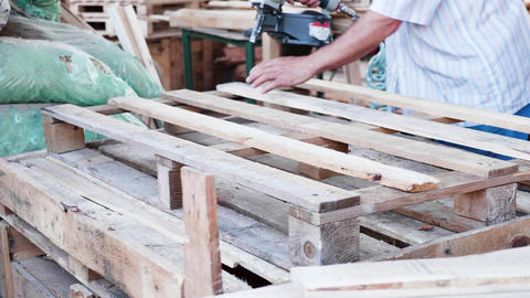 Man Worker in a timber factory using a nail gun to make a wooden pallet Live Action