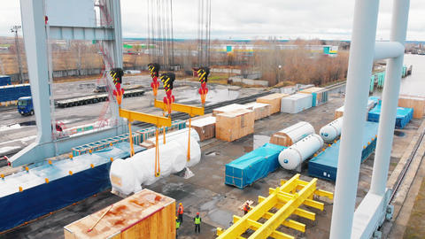 Cargo port - A big industrial crane moving the cargo in the air - workers in Live Action