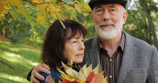 Elderly couple hugging. Senior man hugs his sick wife under an autumn tree , she Live Action