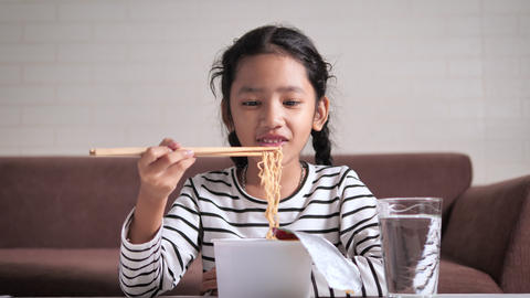 Little Asian girl eating hot and spicy instant noodle with happiness select focus shallow depth of GIF