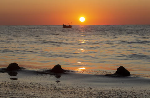 Sunrise with reflection and a boat on the beach フォト