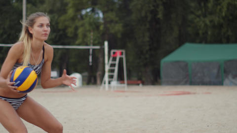Young woman holding a volleyball in her hands, throwing it from hand to hand, 4k Live Action
