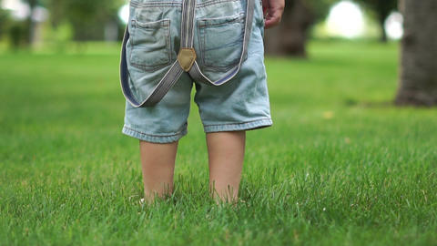 Little barefoot boy's feet stomping on green grass close up in slow motion Live Action