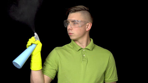 A young man shoots out of a spray of water, like a gun. A man in safety glasses Footage