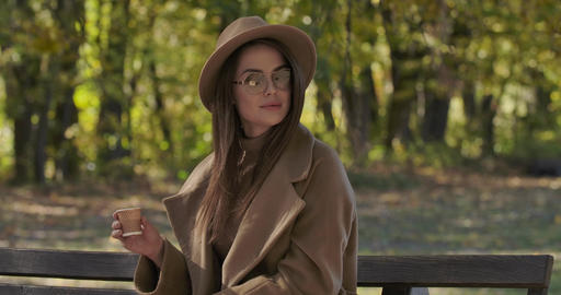 Charming Caucasian lady in sunglasses and brown hat sitting on bench with the Footage
