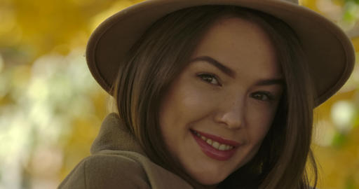 Close-up face of young charming European woman in brown hat posing at camera on Live Action