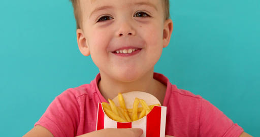 Cute boy sharing french fries with camera Live Action
