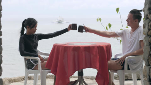 Young couple on honeymoon drinking coffee at the cafe table with ocean view Live Action