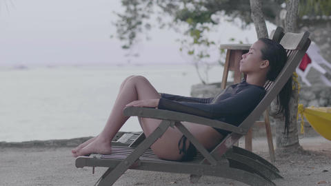 Young woman sitting on beach's chair relaxing in the tranquil beach resort Footage