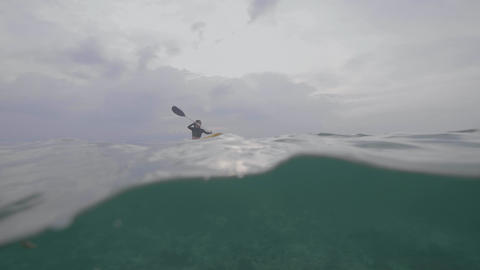 Split shot of a woman paddling the kayak in calm sea with underwater view Footage