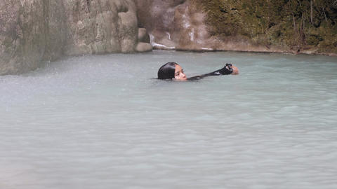 Young lady relaxing in tropical natural water swimming in rainforest waterfall Footage