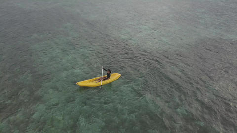Drone point of view: A tourist enjoys kayaking in the peaceful ocean on summer Live Action