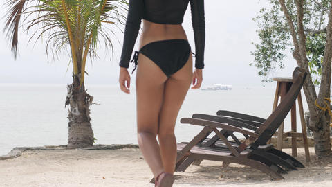 Slim woman wearing sexy swimwear walking on the beach resort and sit on a chair Live Action