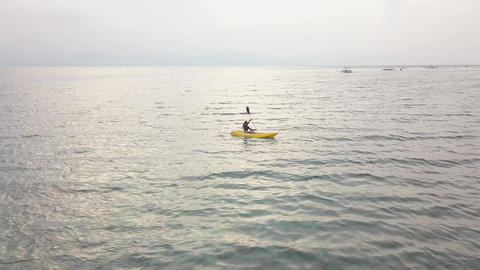 Aerial view: A young female kayaking alone in a serene tropical ocean in summer Footage