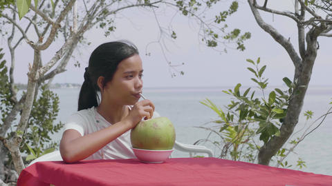 A woman having a relaxing time at tropical resort drinking fresh coconut juice Footage