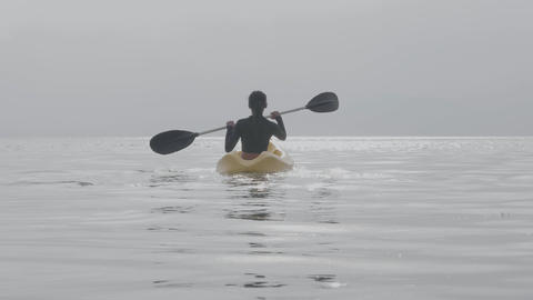 A woman paddleboarding in the middle of peaceful open ocean. Rear view Live Action