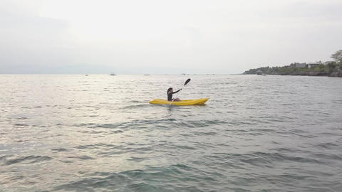 Aerial view of a young toursit enjoys kayaking in the peaceful ocean in summer Live Action