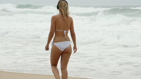 Young and sexy woman has fun on the sandy beach at the Atlantic ocean Footage