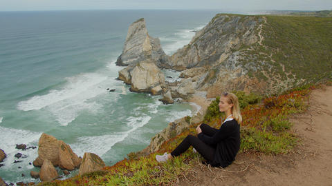 Beautiful woman relaxes at Cabo da Roca in Portugal - Sintra Natural Park Footage