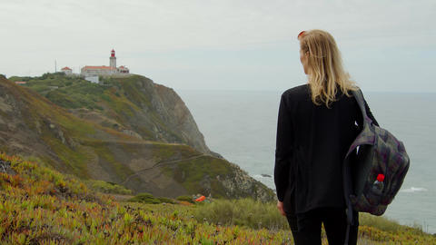 Young traveler at Cabo Da Roca in Portugal at the Atlantic Ocean Live Action