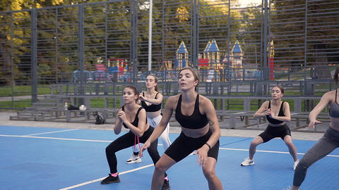 Young slim sporty girls in sportswear doing squat exercises on the sportground Live Action