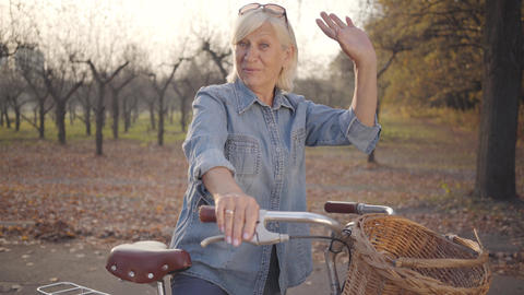 Joyful mature Caucasian lady in denim standing with bicycle and waving at camera Footage