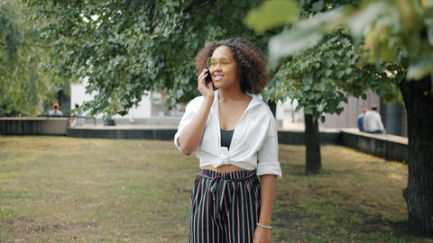 Slow motion of joyful mixed race woman talking on mobile phone outdoors in park Footage